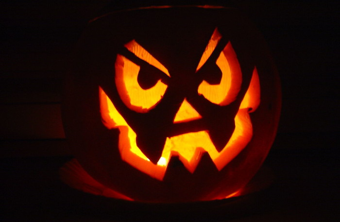 photo of a jack o lantern with a mischievious face, illuminated from within on a black background