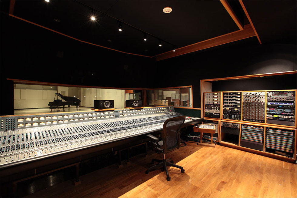 photo of the control room in a recording studio, showing a large mixing board and racks of equipment