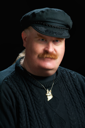 color head shot of Jim in a black turtleneck sweater and Greek fisherman's cap with a gold dog-shaped pendant on a dark background