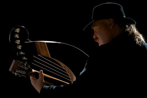 color photo of Jim with his harp guitar, back view, dark background
