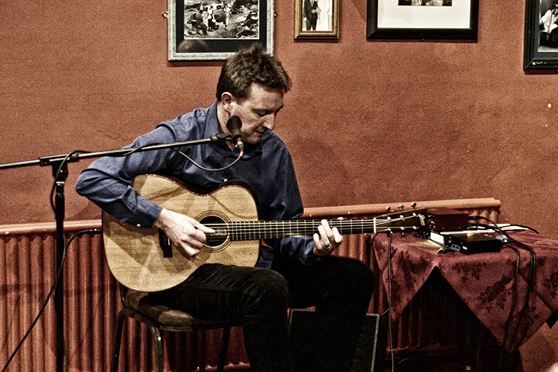 photo of Clive Carroll playing acoustic guitar